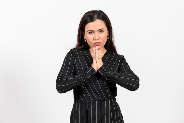 Empleada de oficina en estricto traje negro posando en blanco