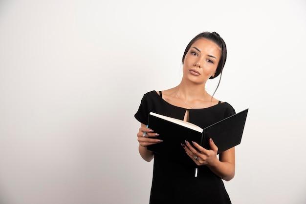 Empleada posando con cuaderno abierto en la pared blanca.