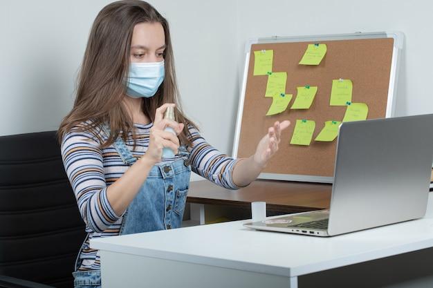Empleada que usa herramientas básicas de desinfección para mantener la oficina estéril