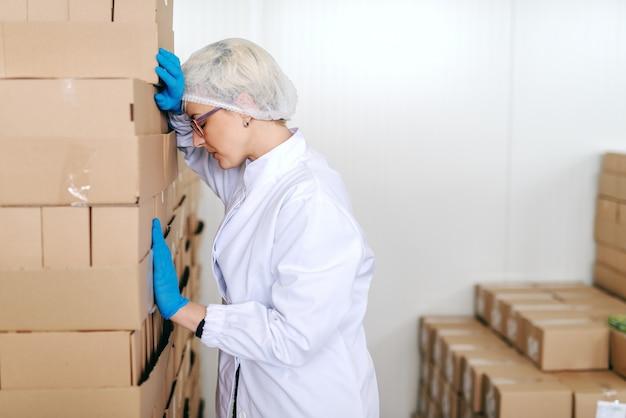 Empleada rubia desesperada en uniforme estéril apoyándose en cajas. interior de la fábrica de alimentos.