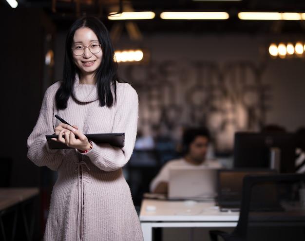 Una empleada tomando notas en su tableta a pie.