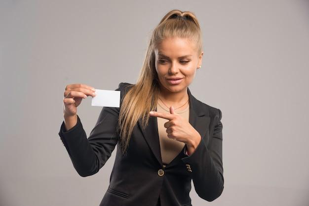 Empleada en traje negro presentando su tarjeta de visita y apuntando a ella.