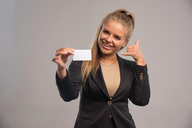 Empleada en traje negro presentando su tarjeta de visita y pidiendo llamada.