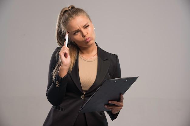 Empleada en traje negro sosteniendo un contrato y pensando.
