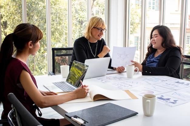 Las empleadas están ofreciendo trabajos al jefe en la sala de reuniones.