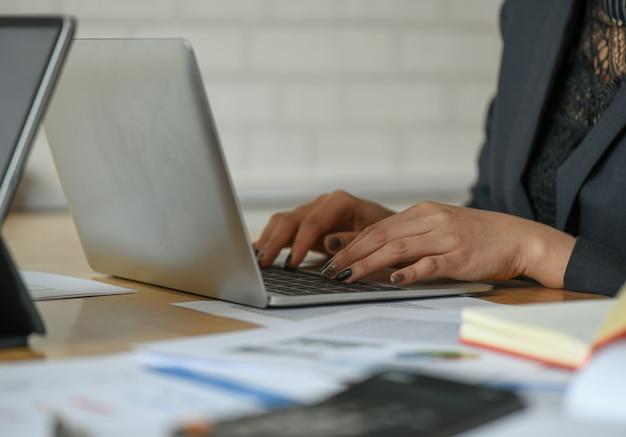 Las empleadas están utilizando una computadora portátil en el escritorio de la oficina.