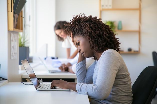 Empleado afroamericano cansado trabajando en proyecto