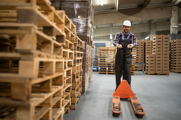 Empleado de almacén calificado empujando transpaleta manual y trabajando en la sala de almacenamiento de la fábrica.