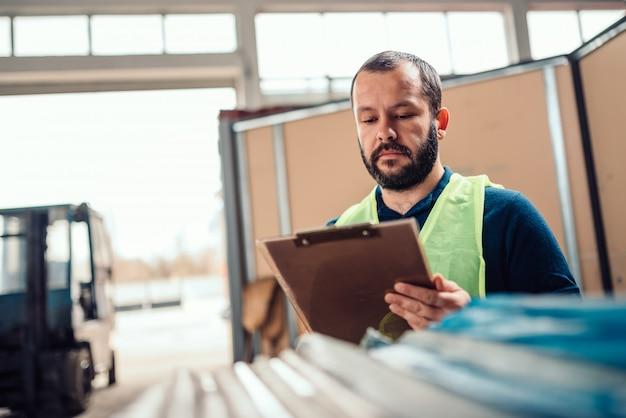 Empleado de almacén que verifica el inventario del almacén en la fábrica del almacén