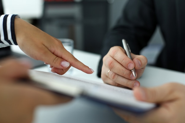 Empleado de bienes raíces señalando dónde debe firmar el visitante