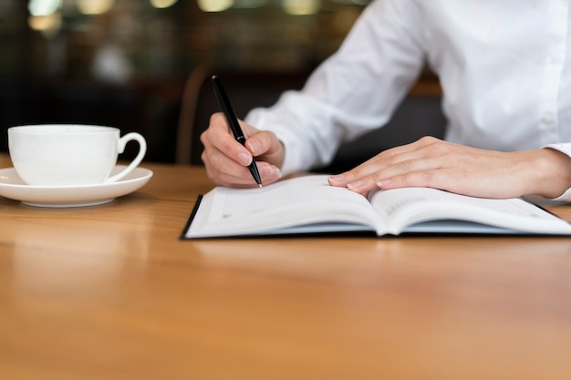 Empleado escribiendo en vista frontal de agenda
