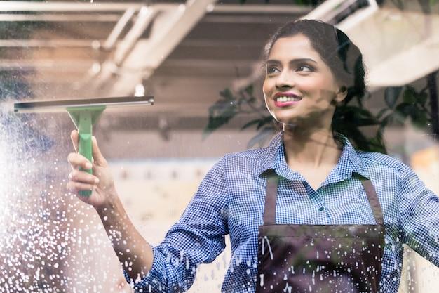 Empleado indio limpiando ventanas