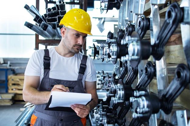Empleado industrial vistiendo uniforme y casco amarillo comprobando la producción en la fábrica.