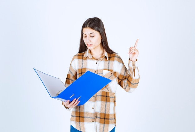Empleado joven hermoso que mira los documentos dentro de la carpeta azul.
