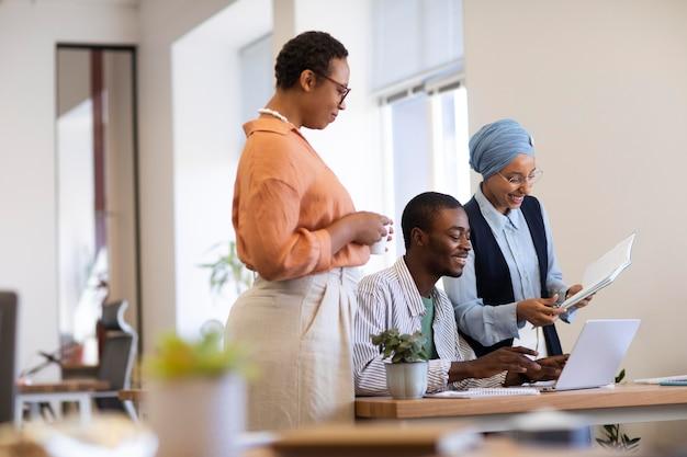 Empleado masculino acostumbrándose a su nuevo trabajo de oficina junto con colegas femeninas