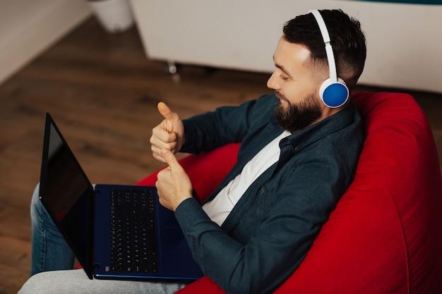 Empleado masculino en auriculares haciendo un gesto de aprobación con los dedos pulgares mientras habla en una videollamada con diversos colegas en la sesión informativa en línea con el portátil en casa.