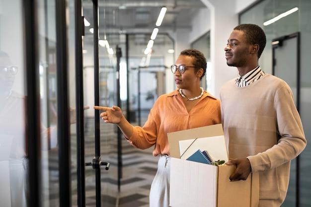 Empleado masculino explorando su nueva ubicación de trabajo de oficina mientras lleva una caja de pertenencias