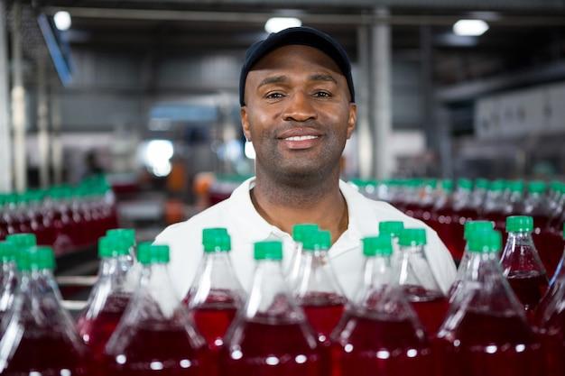 Empleado masculino sonriente de pie junto a botellas de jugo en la fábrica.