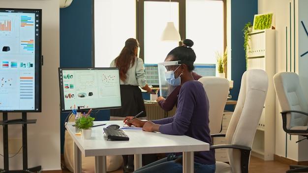 Empleado negro con visera y máscara de protección apuntando en el escritorio analizando estadísticas financieras tomando notas en el portapapeles en la nueva oficina comercial normal. equipo multiétnico respetando la distancia social.