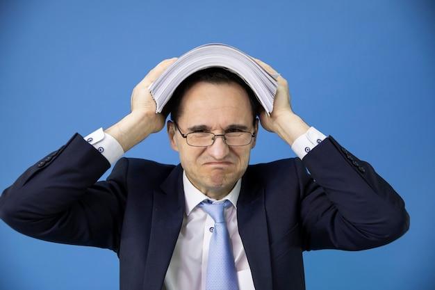 Empleado de oficina abrumado con exceso de trabajo se cubrió la cabeza con una pila de documentos