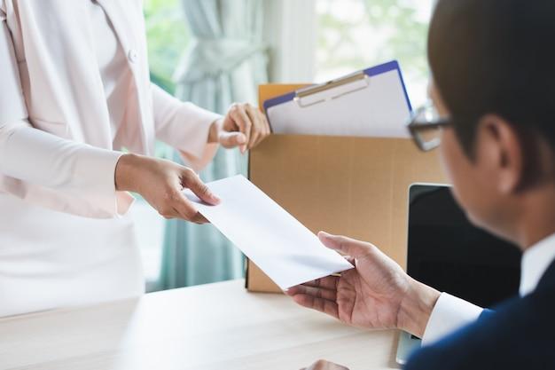 Empleado de oficina enviando carta de renuncia al gerente.