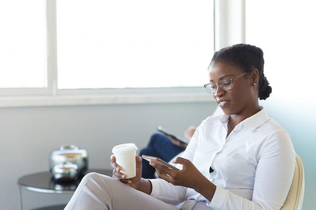 Empleado de oficina feliz revisando mensajes en celular