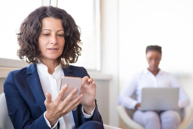 Empleado de oficina femenino con web de navegación celular