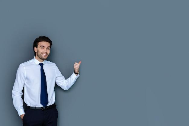 Empleado de oficina. hombre agradable seguro inteligente sonriendo y apuntando a la pared mientras trabaja en la oficina