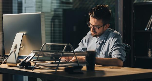 Empleado de oficina inteligente a altas horas de la noche