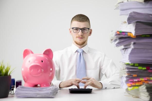 Empleado de oficina inteligente calcula facturas, mucho papeleo, gran alcancía en el escritorio