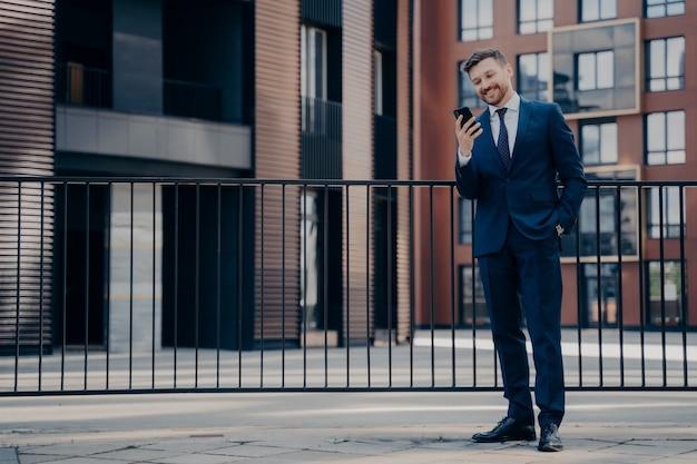 Empleado de oficina masculino guapo sonriente vestido con traje azul revisando su teléfono mientras se toma un descanso, revisando mensajes y notificaciones, parado solo afuera con un moderno edificio de oficinas detrás