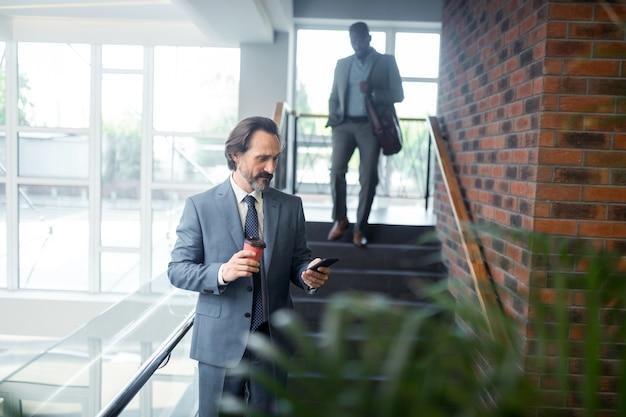 Empleado de oficina. mensaje de lectura de oficinista canoso barbudo en smartphone de pie junto a la escalera