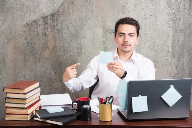 Empleado de oficina mostrando su bloc de notas en el escritorio de oficina.