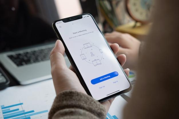 Un empleado que trabaja desde casa está descargando la plataforma social de la aplicación zoom