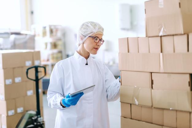 Empleado rubio caucásico en uniforme estéril de pie y tratando con logística de productos. interior de la fábrica de alimentos. tableta en mano.