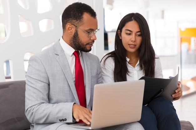 Empleado serio que consulta a un colega y muestra documentos