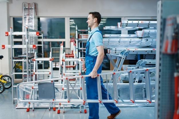 Empleado de sexo masculino en uniforme tiene nuevas escaleras de aluminio en almacén de herramientas. departamento con escaleras, elección de equipo en ferretería, supermercado de instrumentos