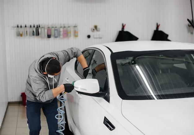 Un empleado sopla y limpia el automóvil después del lavado. lavado de autos.