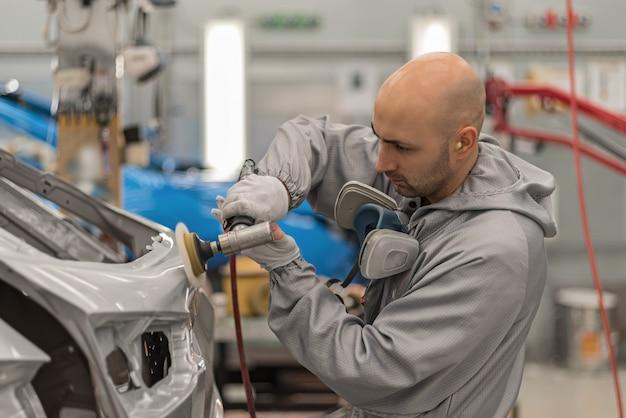 Empleado en el taller de pintura de la carrocería pule partes de carrocería pintadas