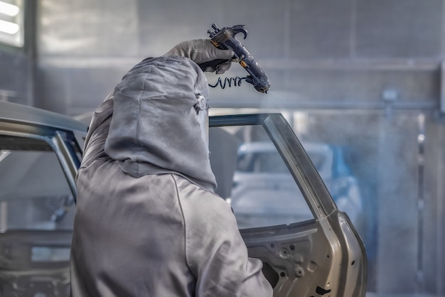 Empleado del taller de pintura de la planta automotriz pinta los elementos del automóvil.