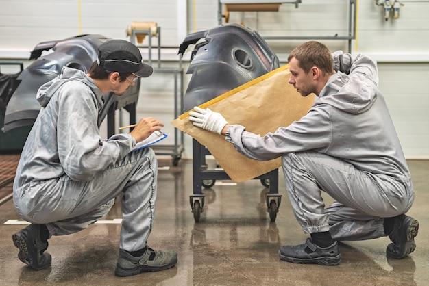 Un empleado del taller de pintura de la planta automotriz realiza capacitación sobre la preparación de parachoques para pintar