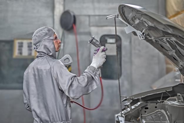 Empleado del taller de pintura prepara la carrocería para pintar.