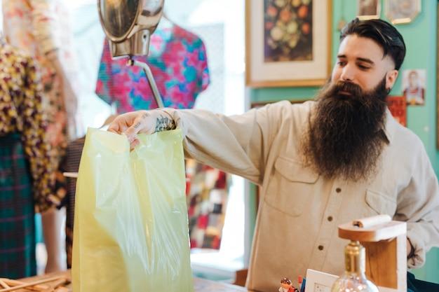 Empleado de la tienda amigable le da a un cliente su bolso en la tienda de ropa
