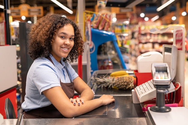 Empleado de ventas bastante joven en delantal sentado junto a la caja registradora en el supermercado y mirándote con una sonrisa mientras atiende a los clientes
