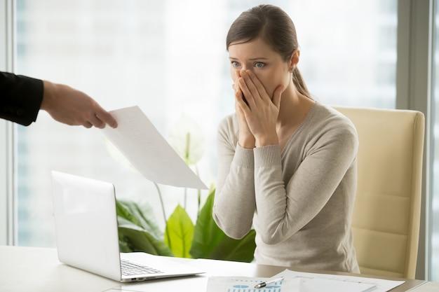 Empleador dando aviso de despido a mujer joven