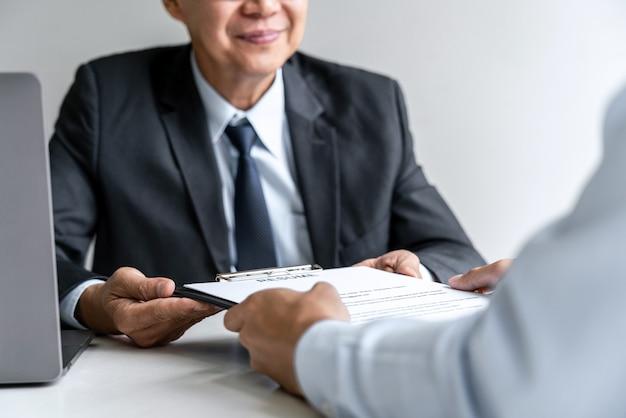 El empleador se entrevista para pedir al solicitante masculino para la contratación hablando en la oficina