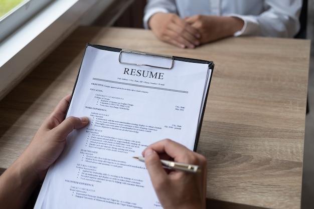 Empleador entrevistando a un joven hombre que busca trabajo sentado en una mesa leyendo su cv visto desde