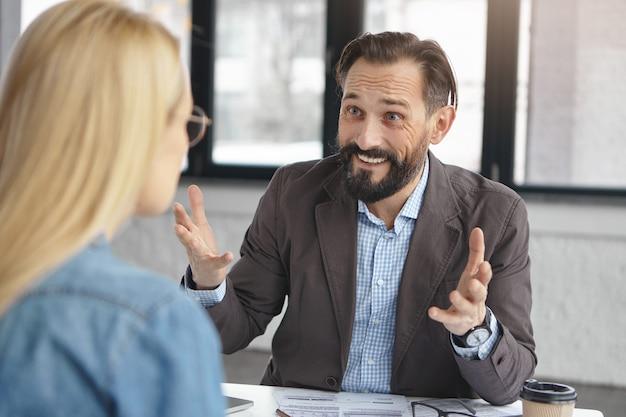 Empleador hombre barbudo exitoso entrevista a mujer para trabajo