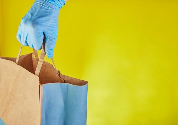 El empleador del hombre de entrega en guantes azules sostiene la bolsa de papel del arte con la comida, aislada en estudio amarillo. servicio de cuarentena del virus del coronavirus pandémico concepto 2019-ncov. copia espacio