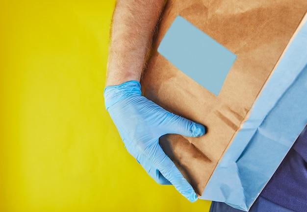 El empleador del hombre de entrega en guantes azules sostiene la bolsa de papel del arte con la comida, aislada.